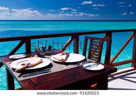 Table setting at tropical beach restaurant - stock photo