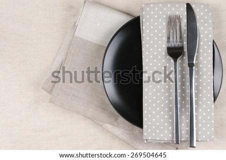Table setting: black plate, fork and knife with napkins on linen tablecloth. Top view point. - stock photo