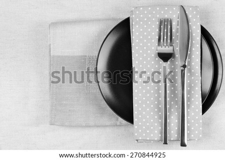 Table setting: black plate, fork and knife with napkins on linen tablecloth. Top view point. Monochrome black and white image. - stock photo