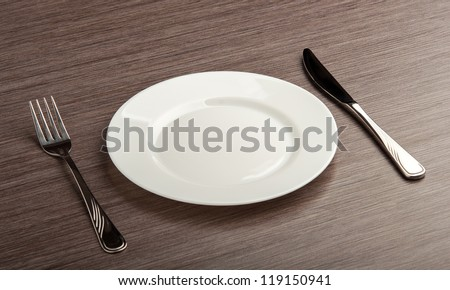 table setting. empty white plate with knife and fork - stock photo