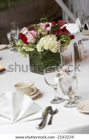 table setting for a wedding or dinner event, very shallow depth of field with the focus on the flowers, blurry forground.