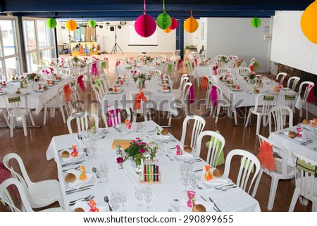 Table setting for an wedding reception in orange, pink and yellow color - stock photo