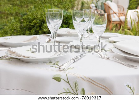 Table setting for garden banquet with expensive table cloth, silverware, and wine glasses - stock photo