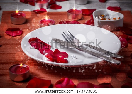 Table setting for lovers with rose petals - stock photo