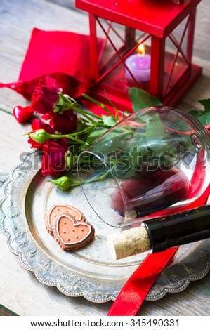 Table setting for St. Valentines day with glasses of red wine, present box and red roses  in rustic style