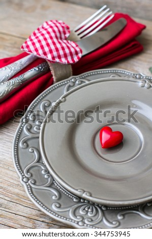 Table setting for St. Valentines day with glasses of wine, present box and red roses  in rustic style
