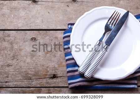 Table setting for summer. Knife and fork on white  plate on aged wooden background. Selective focus.