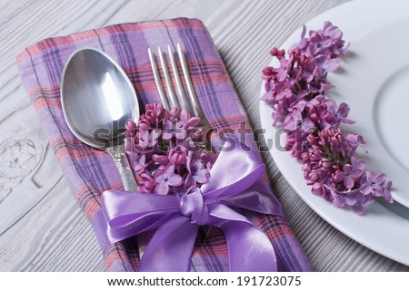 table setting in purple colors, decoration flowers fragrant lilacs. close-up view from above  - stock photo