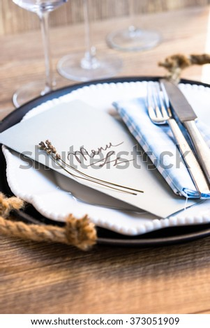 Table setting in restaurant with menu, wine glasses and plate