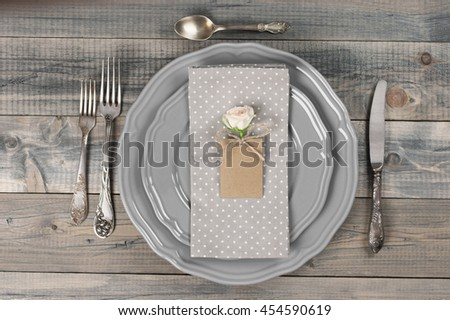 Table setting in rustic style on wooden table: gray plates, vintage silverware, linen napkin and blank rough tag with rose flower. Top view point.