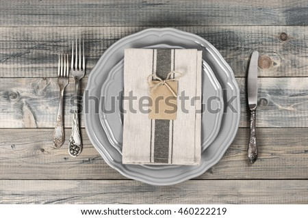 Table setting in rustic style on wooden table: gray plates, vintage silverware, linen napkin and blank rough tag. Top view point.