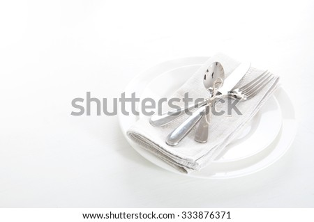 Table setting in white and gray colors with linen napkins and silverware - stock photo