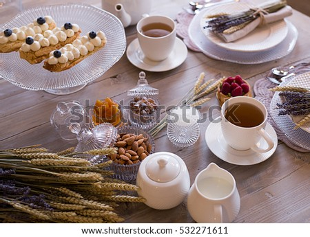Table setting. Morning Breakfast with tea and cakes decorated with wheat and lavender