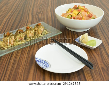 Table setting of a light meal of raw salmon salad and cooked salmon maki sushi topped with roe and serve with pickled ginger and wasabi. - stock photo