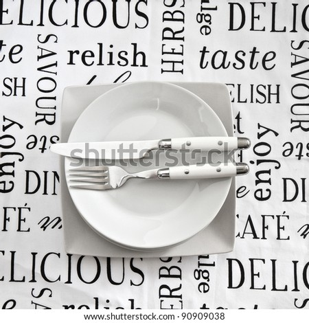 Table setting on printed tablecloth with cutlery and plates - stock photo