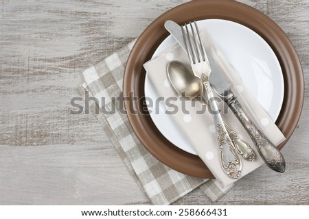 Table setting: plates, vintage fork, knife and spoon with napkin on rustic wooden table. Top view point. - stock photo