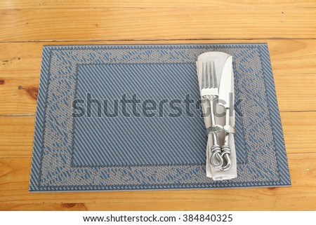 Table setting. Top view of fork and knife hold in metal napkin ring with napkin, on a plate mat. All set on wooden table. - stock photo