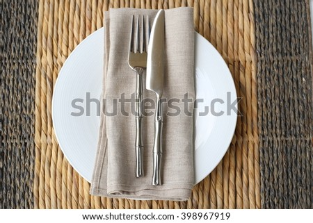 Table setting. Top view of fork and knife with napkin put on white porcelain plate, all set on plant fiber plate mat. - stock photo