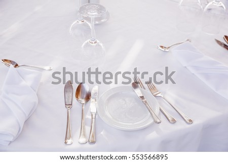 table setting with a white tablecloth in a restaurant.