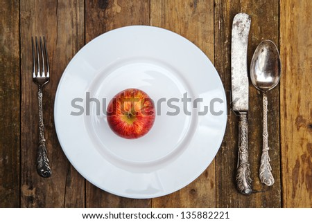 table setting with an apple on a plate - stock photo