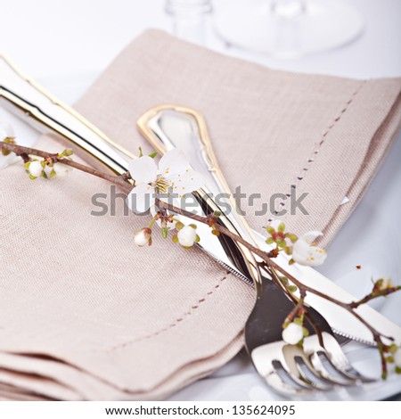 Table setting with blossoming spring flowers - stock photo