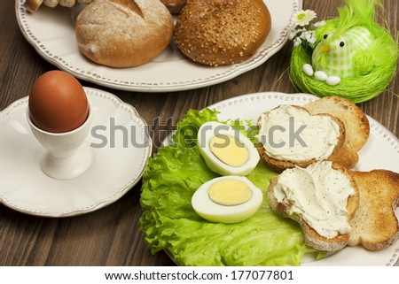 Table setting with Boiled eggs with  cheese cream and easter decorations - stock photo