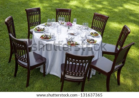 Table setting with chairs for garden banquet - stock photo
