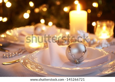 Table setting with Christmas decorations and Christmas tree in a background. - stock photo