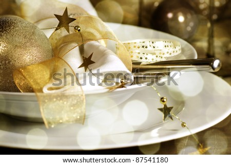 Table setting with Christmas decorations in gold - stock photo