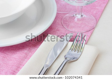 Table setting with fork, knife, plates and napkin