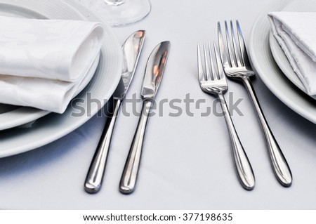 Table setting with fork, knife, plates and napkin.