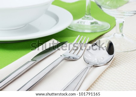 Table setting with fork, knife, spoon, plates, and napkin - stock photo