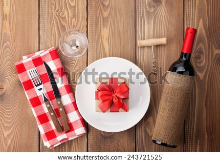 Table setting with gift box on plate, wine glass and red wine bottle. View from above over rustic wooden table background - stock photo