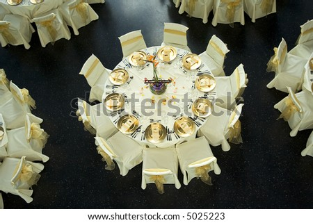 Table setting with golden plates and heart shapes on napkins plus scattered fresh rose petals for a wedding or romantic dinner event - stock photo