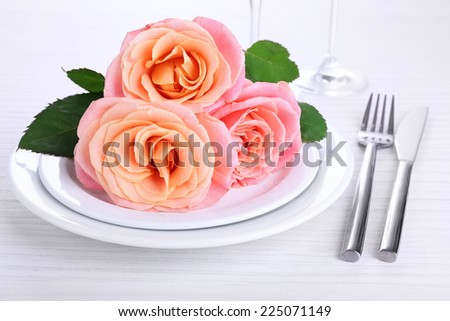 Table setting with pink rose on plate - stock photo
