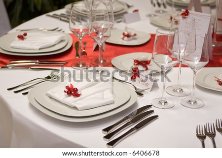 Table setting with plates and silverware (in red and white) - stock photo