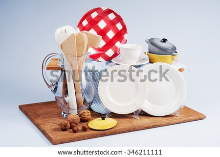 Table setting with plates, cups, napkin, bottles and jug with wooden kitchenware on a wooden board - stock photo