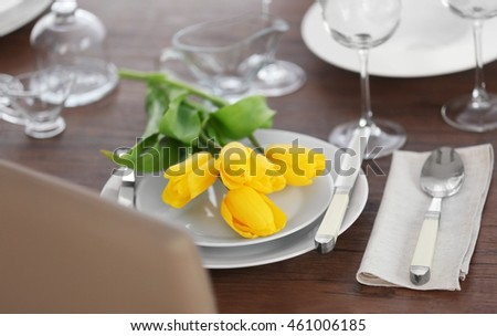 Table setting with plates, cutlery and yellow tulips