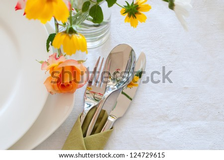 Table setting with plates, silverware and flowers - stock photo