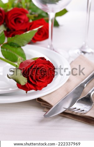 Table setting with red rose on plate  - stock photo