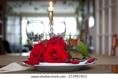 Table setting with red roses on plate - celebrating Valentine's - stock photo
