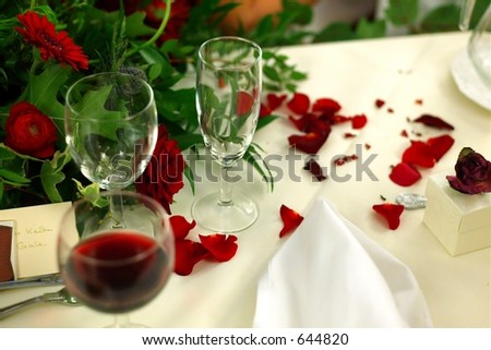 Table Setting with red wine and petals - stock photo