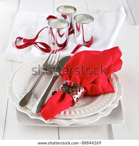 Table setting with silverware, red napkin, candles and decoration for Christmas - stock photo