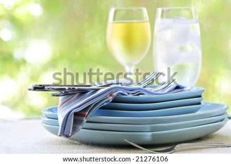 Table setting with stack of plates and cutlery - stock photo