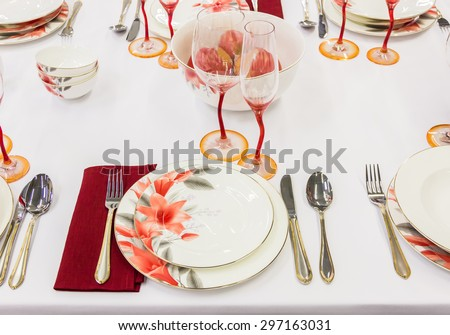 Table setting with tableware, cutlery and a red glass - stock photo