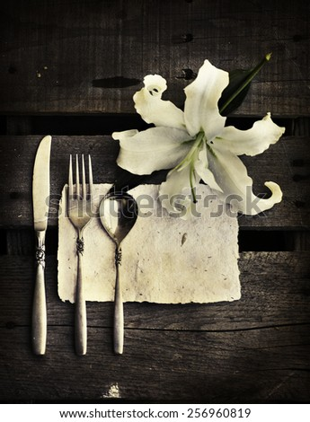 Table setting with vintage old cutlery on wooden table background, white lily flower - stock photo