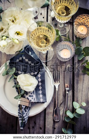 Table setting with white flowers, candles and glasses of champagne on an old vintage rustic wooden table. Vintage summer wedding table decoration, top view. - stock photo