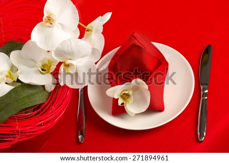 Table setting with white orchid flowers on red tablecloth - stock photo