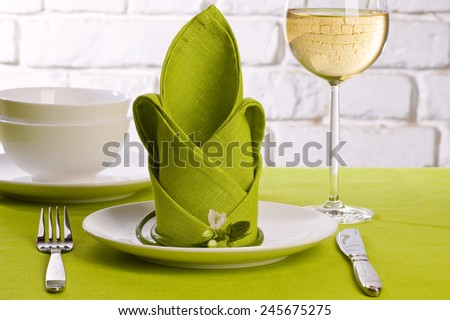 Table setting with white water liliy flowers on green tablecloth on brick wall background - stock photo