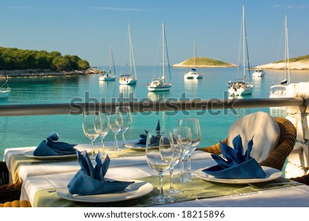Table settings at restaurant on island's seaside with lagoon - stock photo